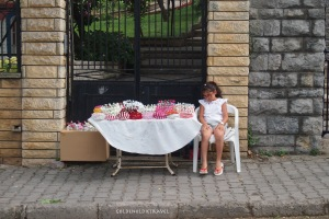 Little girl selling head bands and floral decorations